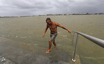 Ray Leon walks up steps after swimming in the Mississippi River Friday, July 12, 2019, in New Orleans, ahead of Tropical Storm Barry. The National Weather Service in New Orleans says water is already starting to cover some low lying roads as Tropical Storm Barry approaches the state from the Gulf of Mexico. (AP Photo/David J. Phillip)