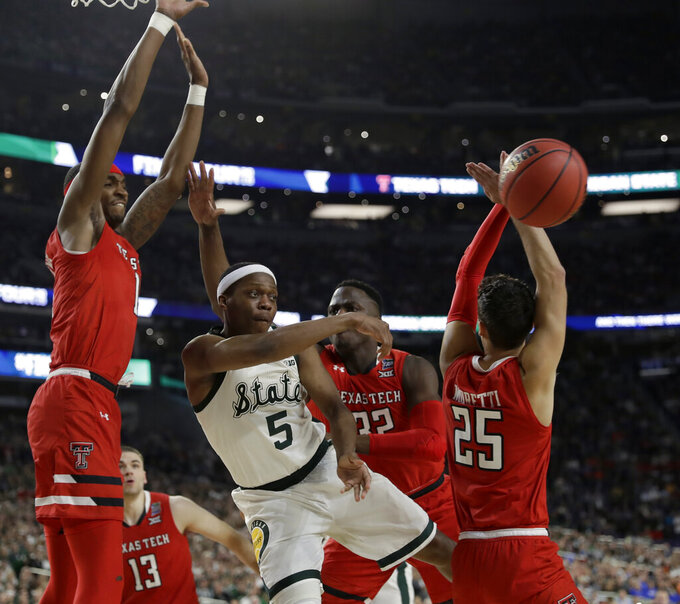 Michigan State's Cassius Winston (5) passes the ball around Texas Tech's Davide Moretti (25) during the first half in the semifinals of the Final Four NCAA college basketball tournament, Saturday, April 6, 2019, in Minneapolis. (AP Photo/David J. Phillip)