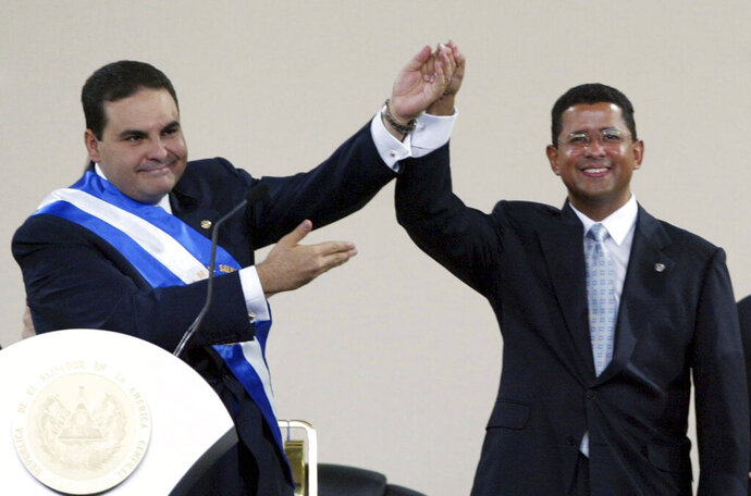 FILE - In this June 1, 2004 file photo, El Salvador's President Tony Saca, left, congratulates former President Francisco Flores, right, after being sworn in as president at the International Fairgrounds in San Salvador, El Salvador. A court in El Salvador has absolved on Friday, July 5, 2019, the two former presidents and three other defendants of criminal responsibility in the alleged diversion of $10 million donated by Taiwan to help victims of 2001 earthquakes (AP Photo/Presidency/Handout, File)