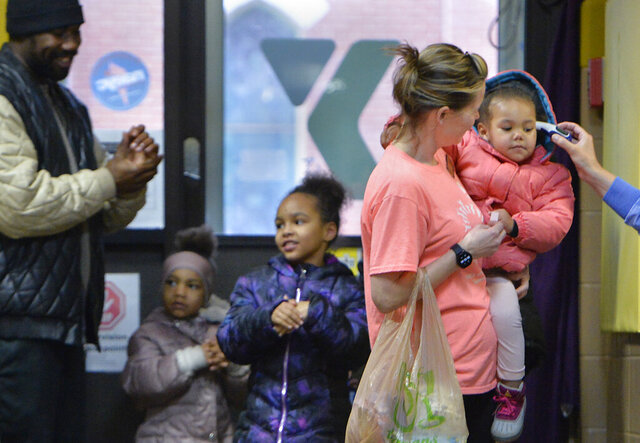 From far left to right, Victor Bibbs, 26, and his daughters Kavaya Bibbs, 4, and Zi'yona Calkins, 7, use hand sanitizer as YMCA childcare employee April Moskalczyk holds two-year-old Zavaya Bibbs, having her temperature taken, on April 1, 2020, in Erie, Pa. Bibbs and the girls' mother dropped their three daughters off at the YMCA for the first time because the youngsters' schools are closed due to the COVID-19 coronavirus. (Greg Wohlford/Erie Times-News via AP)