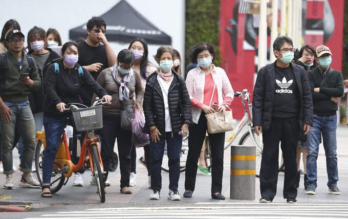People wearing face masks to protect against the spread of the coronavirus cross an intersection in Taipei, Taiwan, Tuesday, Nov. 10, 2020. (AP Photo/Chiang Ying-ying)