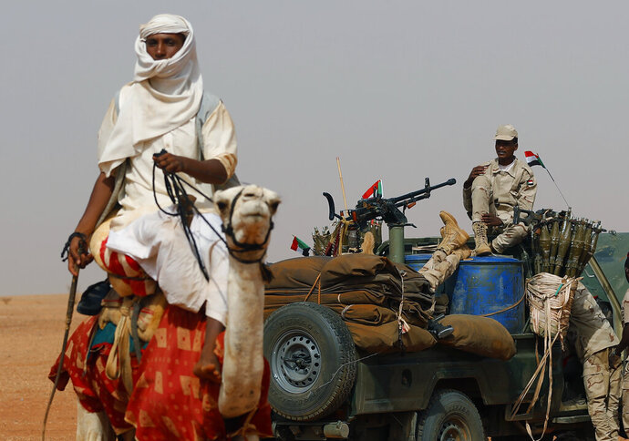 FILE - In this June 22, 2019 file photo, Gen. Mohammed Hamdan Dagalo, the deputy head of the military council sits on his vehicle surrounded by soldiers from the Rapid Support Forces, RSF, unit during a military-backed tribal rally, in the East Nile province, Sudan. On Wednesday, Oct. 30, 2019, Sudanese officials said Sudan has drawn down its forces taking part in a Saudi-led coalition at war with Yemen's rebels. They declined to disclose how many troops have left Yemen and how many remain, but say