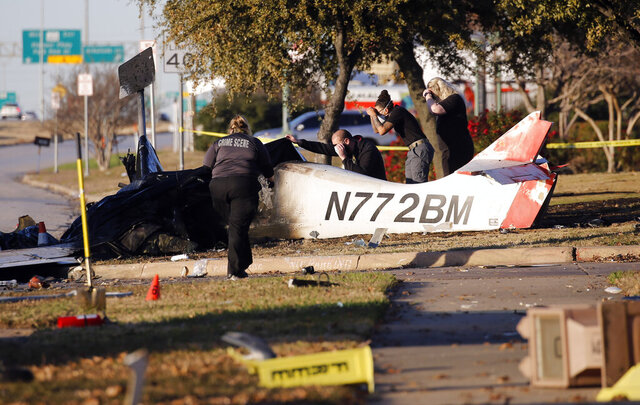 In this Monday, Dec. 21, 2020 photo, officials work at the scene of the fatal plane crash of a single-engine Wheeler Express CT near the intersection of Mayfield Road and Highway 360 in Grand Prairie, Texas. (Vernon Bryant/The Dallas Morning News via AP)