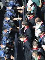 Riot police officers stand at a security barricade as lawyers try to walk to the parliament, in Ankara, Turkey, Friday, July 10, 2020. Turkey's Bar Associations continue to protest against the government's plans to amend laws regulating on lawyers and their associations. (AP Photo/Burhan Ozbilici)