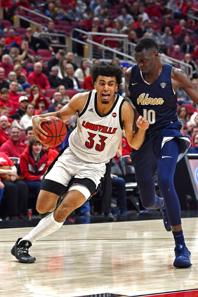 Louisville forward Jordan Nwora (33) attempts to drive past the defense of Akron center Deng Riak (10) during the second half of an NCAA college basketball game in Louisville, Ky., Sunday, Nov. 24, 2019. (AP Photo/Timothy D. Easley)