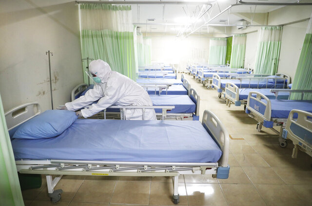 A medics inspects makeshift isolation rooms at Patriot Candrabhaga stadium prepared to become a quarantine facility for people showing symptoms of the COVID-19 amid the new coronavirus outbreak in Bekasi on the outskirts of Jakarta, Indonesia, Wednesday, Sept. 9, 2020. While Indonesia has recorded more deaths from the coronavirus than any other Southeast Asian country, it also has seen by far the most fatalities among medical workers in the region, leading to concerns about the long-term impact on the nation's fragile healthcare system. (AP Photo/Achmad Ibrahim)