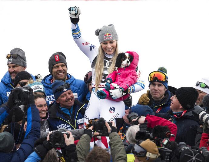 Lindsey Vonn of the United States celebrates with the dog Lucy after the flower ceremony of the women downhill race at the 2019 FIS Alpine Skiing World Championships in Are, Sweden Sunday, Feb. 10, 2019. (Jean-Christophe Bott/Keystone via AP)