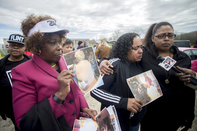 Detroit attorney Cynthia M. Lindsey stands alongside her clients Buffi Clements, 42 at center, and her sister Brandi as they talk about the death of their father Joseph C. Clements, who passed away from kidney cancer in July 2017 during a rally on the five-year anniversary of the Flint water crisis on Thursday, April 25, 2019 outside of the Flint, Mich., water plant. Buffi Clements said their family believes his cancer was caused by drinking Flint tap water following the switch, and are currently part of a class action lawsuit. (Jake May/MLive.com/The Flint Journal via AP)