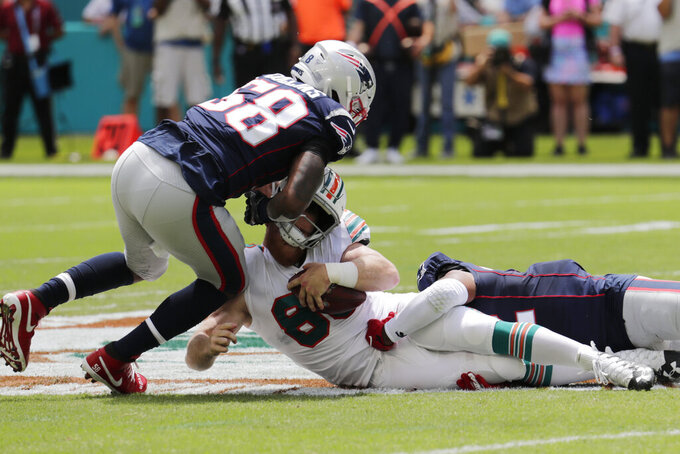 New England Patriots outside linebackers Jamie Collins (58) and Elandon Roberts (52) sack Miami Dolphins quarterback Ryan Fitzpatrick (14), during the first half at an NFL football game, Sunday, Sept. 15, 2019, in Miami Gardens, Fla. (AP Photo/Lynne Sladky)