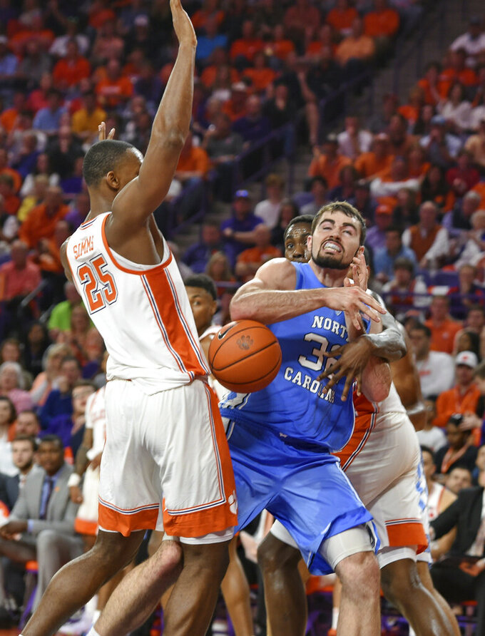 North Carolina's Luke Maye, center, loses the ball between Clemson's Aamir Simms, left and Elijah Thomas during the first half of an NCAA college basketball game Saturday, March 2, 2019, in Clemson, S.C. (AP Photo/Richard Shiro)