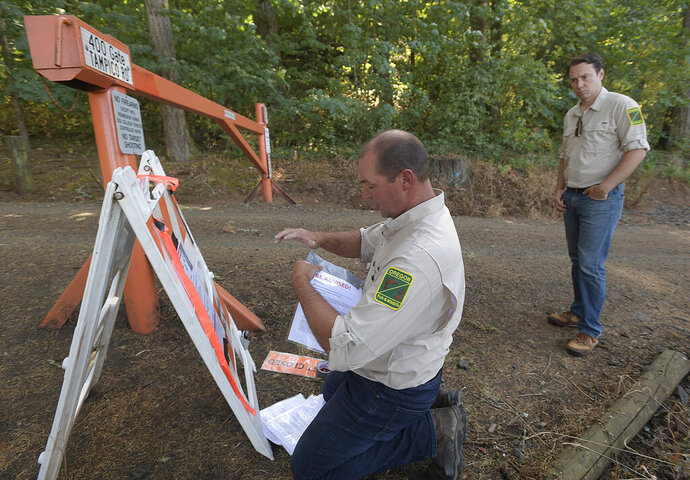 RETRANSMISSION TO CORRECT TO FOUR DAYS - Oregon Department of Fish and Wildlife South Willamette Watershed District Manager Brian Wolfer removes closure signs and posts cougar informational signs at an entrance to the Dunn Research Forest after trackers killed a cougar thought to be involved in an incident while Oregon Department of Fish and Wildlife Public Information Officer Adam Baylor watches Wednesday, Sept. 4, 2019 in Corvallis, Ore. Four days after a cougar chased a jogger in an Oregon forest, wildlife officials on Wednesday tracked down and killed a mountain lion believed to be the same animal.  (Mark Ylen/Albany Democrat-Herald via AP)