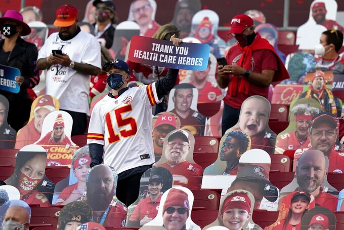 A fan holds up a sign honoring heart care workers before the NFL Super Bowl 55 football game between the Kansas City Chiefs and Tampa Bay Buccaneers, Sunday, Feb. 7, 2021, in Tampa, Fla. (AP Photo/Lynne Sladky)