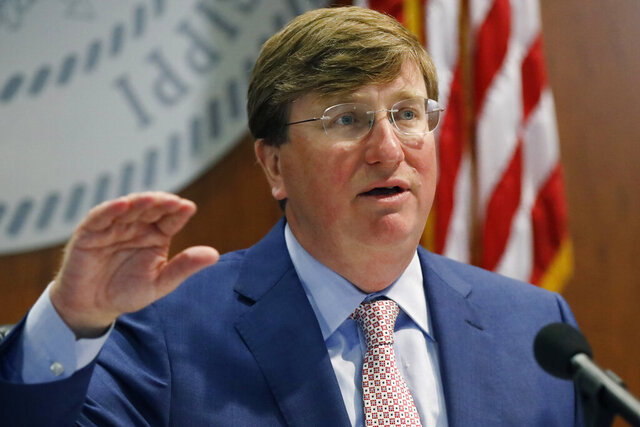 Gov. Tate Reeves discusses his statewide order for people to wear masks in public amid a recent surge in cases of the new coronavirus during a COVID-19 press briefing, Tuesday, Aug. 4, 2020 in Jackson, Miss. Director of the Mississippi Emergency Management Agency Greg Michel and State Health Officer Dr. Thomas Dobbs, also spoke and provided an update on the coronavirus and the state's ongoing strategy to limit transmission. (AP Photo/Rogelio V. Solis)