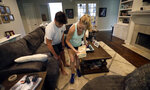 Tiffany Favre, right, and her son, Brandon, use blocks to raise their couch off the floor Friday, July 12, 2019, in Baton Rouge, La., ahead of Tropical Storm Barry. The National Weather Service in New Orleans says water is already starting to cover some low lying roads as Tropical Storm Barry approaches the state from the Gulf of Mexico. (AP Photo/David J. Phillip)