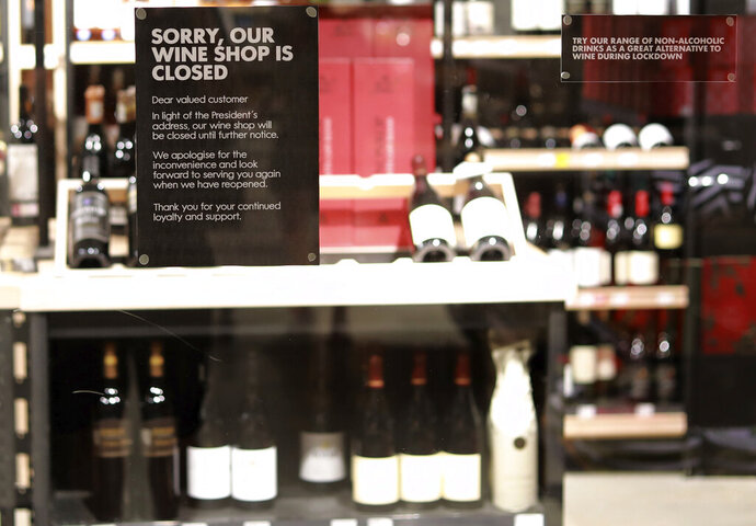 A wine store in Cape Town, South Africa, displays a closed sign at it's entrance Tuesday, Dec. 29, 2020. South African President Cyril Ramaphosa has declared the wearing of masks compulsory and has reimposed a ban on the sales of alcohol and ordered the closure of all bars and beaches as part of new restrictions to help the country battle a resurgence of the coronavirus, including a new variant. (AP Photo/Nardus Engelbrecht)