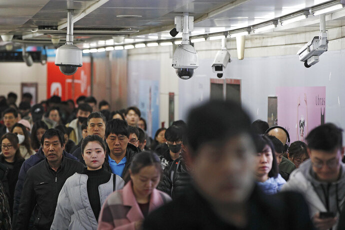FILE - In this Feb. 26, 2019, file photo commuters walk by surveillance cameras installed at a walkway in between two subway stations in Beijing. The Carnegie Endowment for International Peace released a report Tuesday, Sept. 17, that found at least 75 countries are actively using AI tools such as facial recognition for surveillance. The new report says a growing number of countries are following China's lead in deploying artificial intelligence to track citizens. (AP Photo/Andy Wong, File)