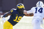 FILE - In this  Saturday, Nov. 28, 2020 file photo, Michigan defensive lineman Kwity Paye (19) reaches in on Penn State quarterback Sean Clifford (14) during the second half of an NCAA college football game in Ann Arbor, Mich. With Oregon's Penei Sewell likely to be long gone, two other heralded tackles could be available to the Vikings at No. 14: Northwestern's Rashawn Slater and Virginia Tech's Christian Darrisaw. Slater has a random connection to Minnesota: His father, Reggie Slater, played in the NBA for the Timberwolves in parts of two seasons.(AP Photo/Carlos Osorio, File)