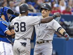 New York Yankees' Mike Tauchman is greeted by teammate Camerom Maybin after hitting a two-run home run against the Toronto Blue Jays during the third inning of a baseball game Thursday, Aug. 8, 2019, in Toronto. (Fred Thornhill/The Canadian Press via AP)