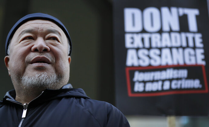 Chinese contemporary artist and activist Ai Weiwei stands with protesters outside the Old Bailey in support of Julian Assange's bid for freedom during his extradition hearing, in London, Monday, Sept. 28, 2020. (AP Photo/Kirsty Wigglesworth)