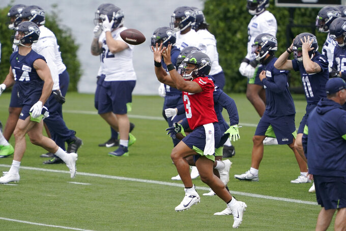 Seattle Seahawks quarterback Russell Wilson (3) catches a football as he runs a drill during NFL football practice Tuesday, June 15, 2021, in Renton, Wash. (AP Photo/Ted S. Warren)