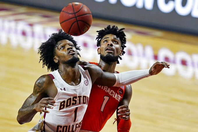 Boston College forward CJ Felder (1) and Syracuse forward Quincy Guerrier (1) battle for position during the first half of an NCAA college basketball game, Saturday, Dec. 12, 2020, in Boston. (AP Photo/Elise Amendola)