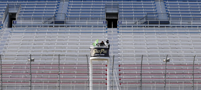 An official waves the green flag to begin a NASCAR Cup Series auto race Sunday, Sept. 27, 2020, in Las Vegas. The race was run without fans due to COVID-19. (AP Photo/Isaac Brekken)
