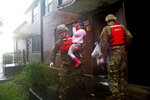 A rescue team from the North Carolina National Guard 1/120th battalion evacuates a family as the rising floodwaters from Hurricane Florence threatens their home in New Bern, N.C., on Friday, Sept. 14, 2018. (AP Photo/Chris Seward)