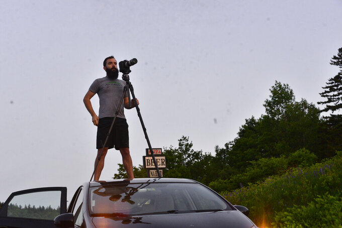 Josh Fields, from Putney, Vt., stands on top of his vehicle to get a clear photograph of the the partial solar eclipse at Hogback Mountain, in Marlboro, Vt., on Thursday, June 10, 2021. (Kristopher Radder/The Brattleboro Reformer via AP)