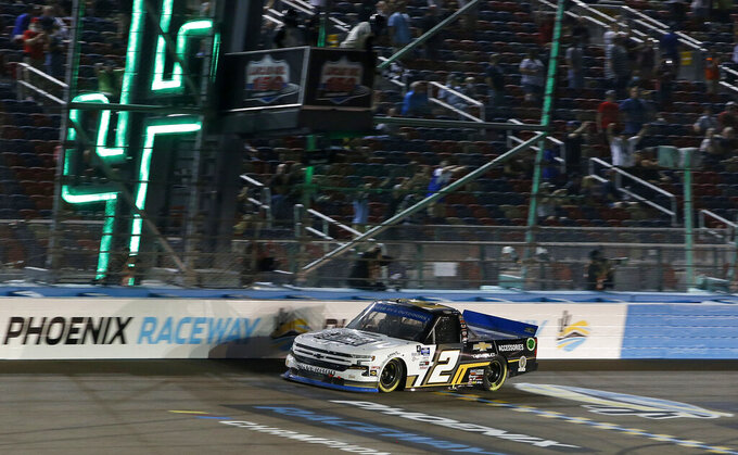Sheldon Creed takes the checkered flag to win the NASCAR Truck Series auto race at Phoenix Raceway, Friday, Nov. 6, 2020, in Avondale, Ariz. With the victory Creed earned the series championship. (AP Photo/Ralph Freso)