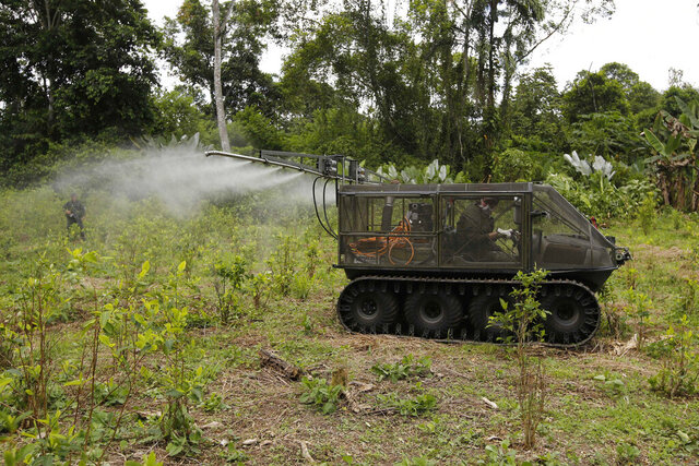 FILE - In this April 18,2018 file photo, a counter-narcotics police officer tests a tactical vehicle to spray herbicides on a coca field in Tumaco, southern Colombia. Colombia's government has proposed in late December 2019 resuming the aerial spraying of coca fields, four years after it was suspended over health concerns. (AP Photo/Fernando Vergara, File)