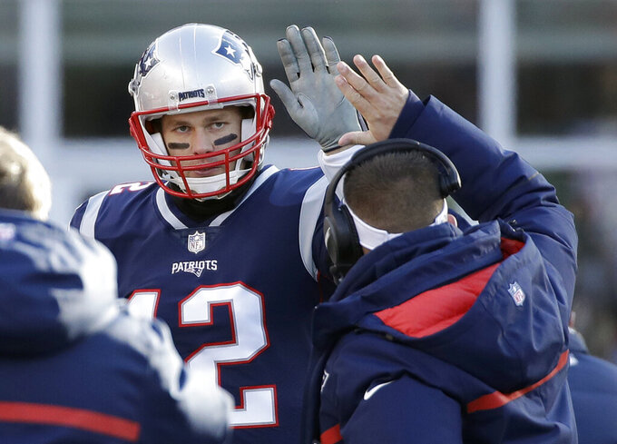 New England Patriots offensive coordinator Josh McDaniels, right, gives a high-five to quarterback Tom Brady during the first half of an NFL divisional playoff football game against the Los Angeles Chargers, Sunday, Jan. 13, 2019, in Foxborough, Mass. (AP Photo/Elise Amendola)