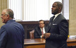 R&B singer R. Kelly, right, appears in court with his attorney Steve Greenberg, March 22, 2019, for a hearing at the Leighton Criminal Court Building in Chicago. An overseas trip by R. Kelly is in limbo after his criminal attorney asked for more time to provide details to the court about concerts the singer wants to perform next month in Dubai. The hearing only briefly touched on a defense motion this week asking the judge in Kelly's sexual-assault case for permission to travel to earn money from up to five concerts.  (E. Jason Wambsgans/Chicago Tribune Via AP, Pool)