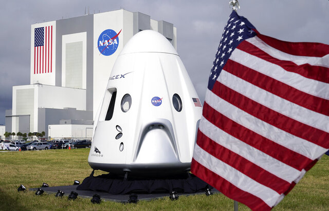 A mockup of the SpaceX crew capsule is seen on display in front of the Vehicle Assembly Building during a news conference at the Kennedy Space Center in Cape Canaveral, Fla., Friday, Nov. 13, 2020. (AP Photo/John Raoux)
