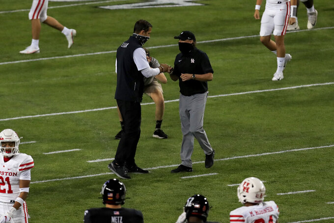 Cincinnati head coach Luke Fickell, center left, fist-bumps Houston head coach Dana Holgorsen, center right, after an NCAA college football game, Saturday, Nov. 7, 2020, in Cincinnati. (AP Photo/Aaron Doster)