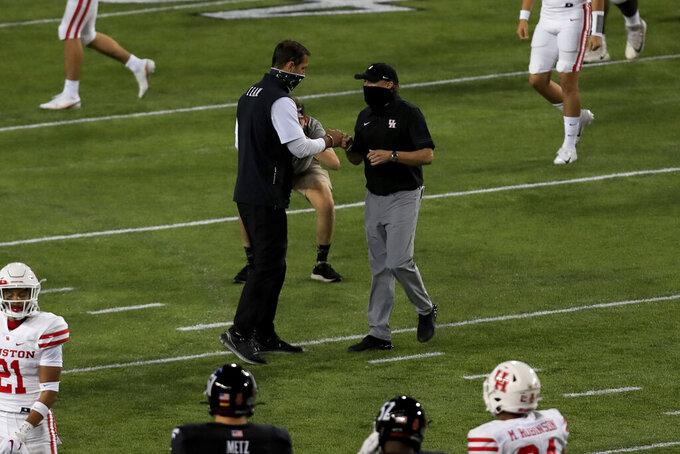 Cincinnati head coach Luke Fickell, center left, fist-bumps Houston head coach Dana Holgorsen, center right, after an NCAA college football game, Saturday, Nov. 7, 2020, in Cincinnati. (AP Photo/Aaron Doster)