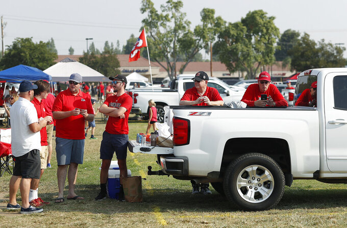 From left to right, Chris Canada, Noah Ewert, Craig Hartman, Ben Wilson, Mike Hartman and Jeff Englund play cards while tailgating prior to kickoff of the Connecticut at Fresno State NCAA college football game in Fresno, Calif., Saturday, Aug. 28, 2021. (AP Photo/Gary Kazanjian)