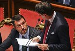 Italian Premier Giuseppe Conte, right, looks at Deputy-Premier Matteo Salvini as he addresses the Senate in Rome, Tuesday, Aug. 20, 2019. Italian Premier Giuseppe Conte blasted the League's leader and Interior minister Matteo Salvini for his decision to spark a government crisis that risks triggering