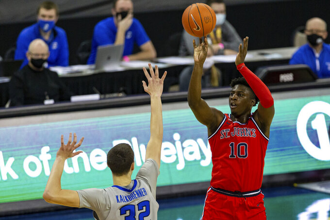 St. John's forward Marcellus Earlington (10) shoots over Creighton center Ryan Kalkbrenner (32) in the first half of an NCAA college basketball game, Saturday, Jan. 9, 2021, in Omaha, Neb. (AP Photo/John Peterson)