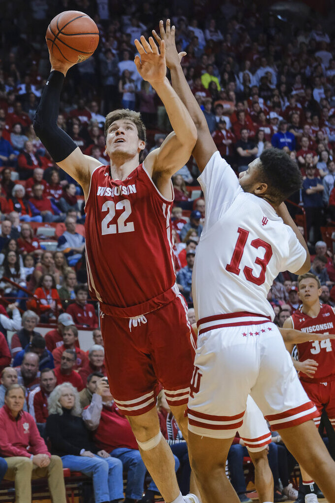 Wisconsin forward Ethan Happ (22) shoots next to Indiana forward Juwan Morgan (13) during the first half of an NCAA college basketball game in Bloomington, Ind., Tuesday, Feb. 26, 2019. (AP Photo/AJ Mast)