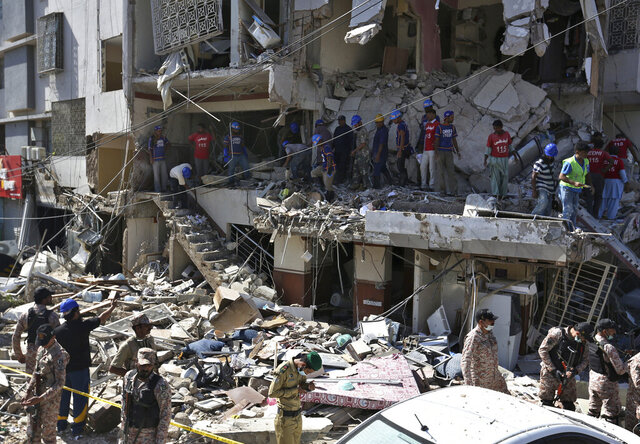 Pakistan's troops and rescue workers look for survivors amid the rubble of a damaged building following the explosion, in Karachi, Pakistan, Wednesday, Oct. 21, 2020. Police and rescuers say a powerful blast has ripped through a multistory building in Pakistan's southern port city of Karachi. (AP Photo/Fareed Khan)