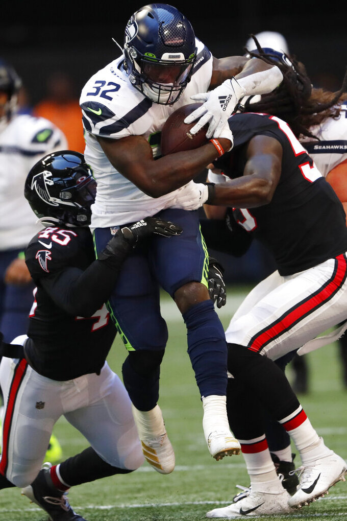 Seattle Seahawks running back Chris Carson (32) runs into Atlanta Falcons linebacker Deion Jones (45) and Atlanta Falcons linebacker Jermaine Grace (53) during the first half of an NFL football game, Sunday, Oct. 27, 2019, in Atlanta. (AP Photo/John Bazemore)