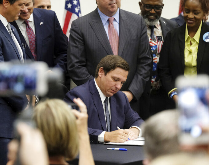FILE - In this Friday, June 14, 2019, file photo, Florida Gov. Ron DeSantis signs the Sanctuary City bill at the Okaloosa County, Fla., commission chambers in Shalimar Fla. The bill requires all law enforcement agencies in Florida to cooperate with federal immigration authorities. U.S. District Judge Beth Bloom on Tuesday, Sept. 21, 2021, rejected parts of the 2019 law banning local government sanctuary policies and requiring local law enforcement to make their best efforts to work with federal immigration authorities. (Michael Snyder/Northwest Florida Daily News via AP, File)