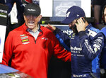 Martin Truex Jr. talks on a phone as he and team owner Joe Gibbs, left, celebrate winning the NASCAR Cup Series auto race at Richmond Raceway in Richmond, Va., Saturday, April 13, 2019. (AP Photo/Steve Helber)
