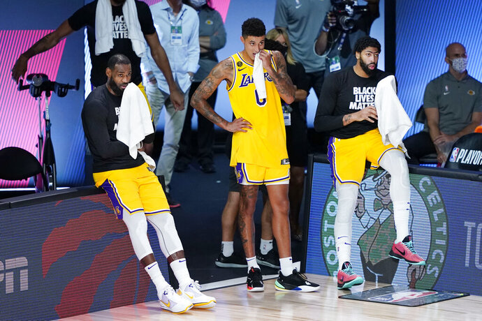 Los Angeles Lakers' LeBron James, left, Kyle Kuzma (0) and Anthony Davis, right, watch the final seconds of the fourth quarter of an NBA basketball first round playoff game against the Portland Trail Blazers Saturday, Aug. 29, 2020, in Lake Buena Vista, Fla. The Lakers won 131-122 to win the series 4-1. (AP Photo/Ashley Landis)
