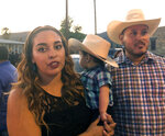 Isabel Regalado, 27, left, her son, Preston Regalado-Soliz, 10-months, and her husband, Esteban Soliz, 38, right, stand in line with thousands of others on Friday, Aug. 16, 2019, to pay respects to Margie Reckard, 63, who was killed by a gunman who opened fire at a Walmart in El Paso, Tex., earlier this month. Thousand of strangers from El Paso and around the country came this weekend to honor Reckard. Her long-time companion, Antonio Basco, says he felt so alone planning her funeral, that he invited the world to join him in remembering his companion of 22 years. (AP Photo/Russell Contreras)