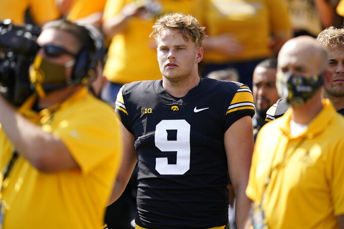 """FILE - Iowa punter Tory Taylor (9) stands on the sideline before an NCAA college football game against Kent State in Iowa City, Iowa, in this Saturday, Sept. 18, 2021, file photo. Tory Taylor sells T-shirts that say """"Punting Is Winning."""" Those words describe what's going on at No. 2 Iowa, where Taylor's punting has played a huge factor in the Hawkeyes' 6-0 start. (AP Photo/Charlie Neibergall, File)"""
