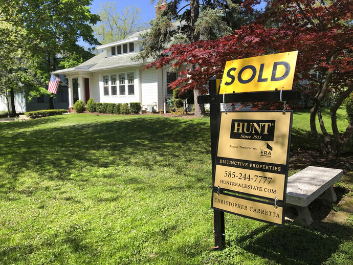 FILE - In this Friday, May 22, 2020, file photo, a sold sign sits in front of a house in Brighton, N.Y. The coronavirus pandemic helped shape the housing market by influencing everything from the direction of mortgage rates to the inventory of homes on the market to the types of homes in demand and the desired locations. (AP Photo/Ted Shaffrey, File)