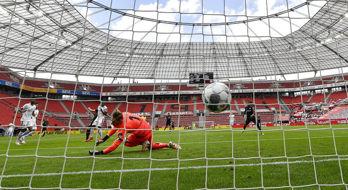 Mainz's goalkeeper Florian Mueller receives the opening goal by Leverkusen's Kevin Volland during the German Bundesliga soccer match between Bayer 04 Leverkusen and FSV Mainz 05 in Leverkusen, Germany, Saturday, June 27, 2020. Because of the coronavirus outbreak all soccer matches of the German Bundesliga take place without spectators. (AP Photo/Martin Meissner, Pool)