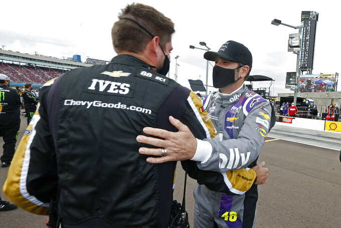 Jimmie Johnson, right, is greeted by opposing team members prior to a NASCAR Cup Series auto race at Phoenix Raceway, Sunday, Nov. 8, 2020, in Avondale, Ariz. (AP Photo/Ralph Freso)