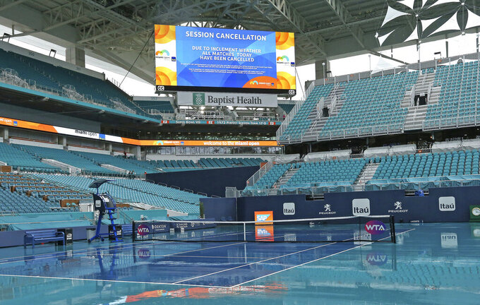 Rain falls on the court after the Miami Open tennis tournament was postponed, Tuesday, March 19, 2019, at Hard Rock Stadium in Miami Gardens, Fla. (David Santiago/Miami Herald via AP)